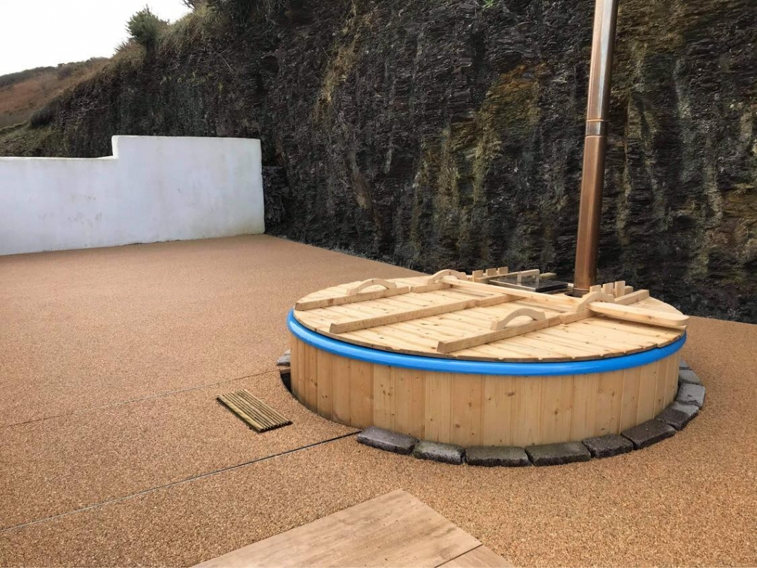 Sustainable resin driveway company, Oltco Cornwall, install a new resin bound patio and hot tub area in Port Isaac
